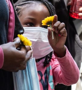 A young girl holds a flower