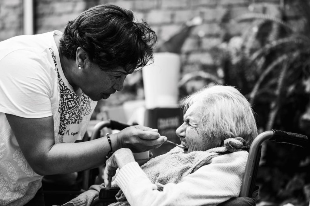 A volunteer with HandsOn Bogotá feeds an elderly woman in Colombia
